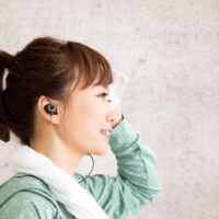 ワイヤレスなイヤフォンを装着してジョギングかウォーキングをする女性